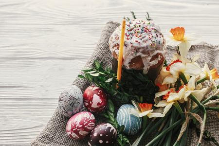 stylish easter bread and painted eggs on rustic wooden background with candle yellow flowers and greenery. happy easter, greeting card. space for text Standard-Bild