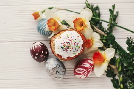 happy easter flat lay, stylish easter bread and painted eggs on rustic wooden background top view with candle yellow flowers and greenery.  greeting card. space for text Standard-Bild