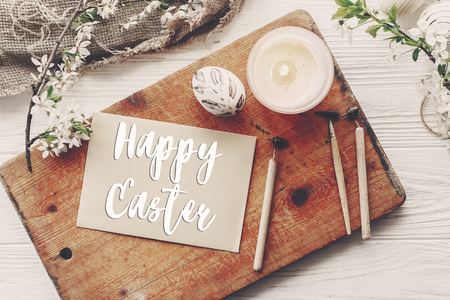 happy easter text flat lay with flowers and stylish eggs on rustic wooden background top view. modern easter greeting card. space for text