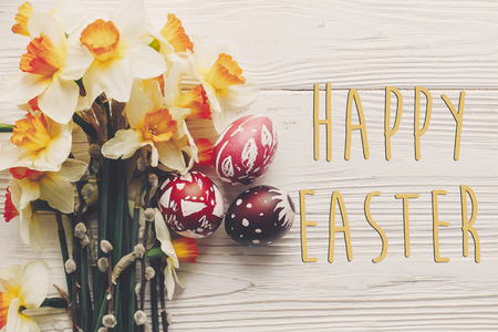 happy easter text flat lay with flowers daffodils and stylish eggs on rustic wooden background top view. modern easter greeting card. space for text Standard-Bild