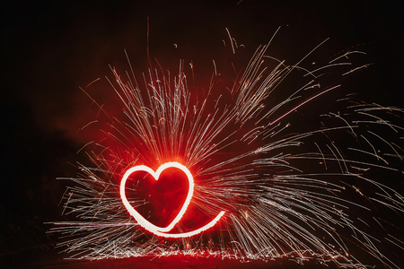 red heart shaped firework with sparkles on black background in night. happy valentines day card. bengal fire burning heart. space for text. wedding or valentine concept
