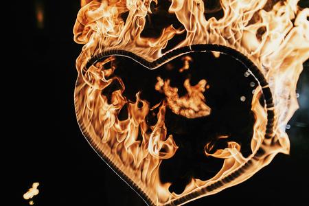 黒い背景にハート型の花火、夜の火災ショー。幸せなバレンタインデーカード。心を燃やすベンガル火災。テキスト用のスペース。結婚式やバレン