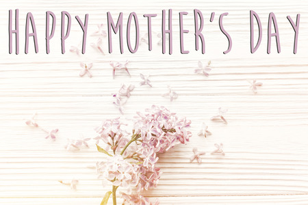 happy mothers day text sign, simple greeting card. spring flat lay with tenderl lilac flowers in soft light on rustic wooden background top view. hello spring. womens day.