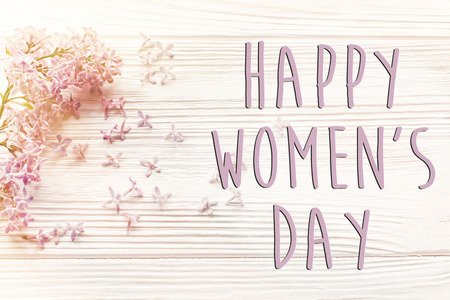 happy womens day text sign, simple greeting card. beautiful lilac flowers on rustic white wooden background top view.  happy mothers woman day. eco. hello spring flat lay image