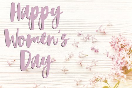 happy womens day text sign, greeting card. hello spring image. beautiful tender lilac flowers and petals in light on white wooden rustic background top view.  happy mothers day 写真素材