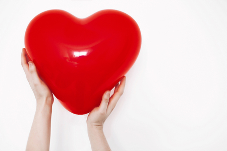 red heart in hands, isolated on white.