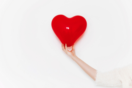 red heart in hand, isolated on white. 版權商用圖片