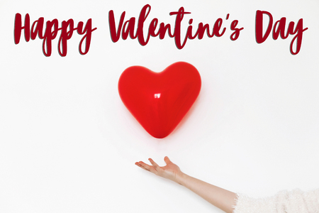 happy valentines day text sign. happy valentines concept. red heart balloon in hands on white background with space for text. greeting card Stock Photo