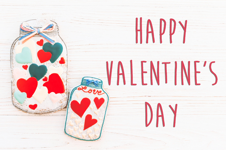 happy valentines day text sign flat lay. cookie hearts in jar and confetti on white rustic wooden background. space for text. greeting card concept. valentines bright image