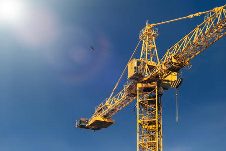 Construction crane tower in sun light beams on background of blue sky. Stockfoto