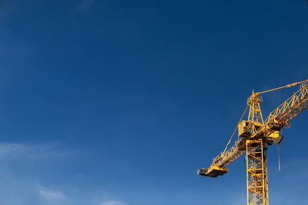 De kraantoren van de bouw op achtergrond van blauwe hemel.