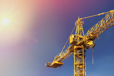Construction crane tower in sun light on background of blue sky.
