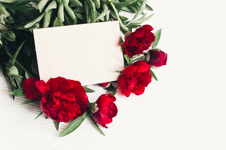 beautiful red peonies bouquet with craft paper on white wooden rustic background.