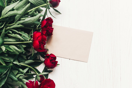 beautiful red peonies bouquet and craft paper card on white wooden rustic background, flat lay. Stock Photo - 96073218