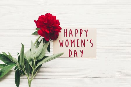 happy womens day text sign on craft card and beautiful red peonies on white wooden rustic background, flat lay. modern greeting card. womens day