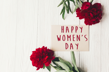 happy women's day text sign on craft card and beautiful red peonies on white wooden rustic background, flat lay. modern greeting card. womens day Stock Photo