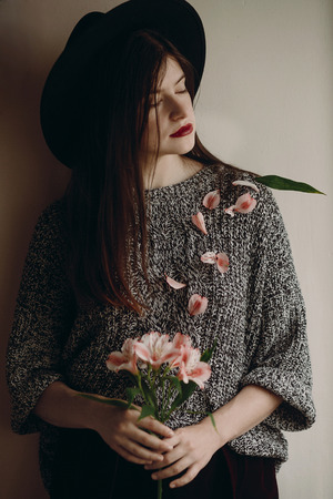 stylish hipster girl in hat holding pink flowers in room. boho woman holding beautiful alstroemeria in hands in spring morning and petals on body. creative sensual female portrait