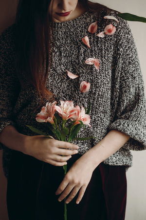 stylish hipster girl in hat holding pink flowers and petals on sweater growing. boho woman holding beautiful alstroemeria in hands in spring morning. creative sensual female portrait