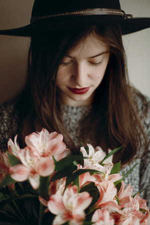stylish hipster girl in hat holding pink flowers in room. boho woman in stylish clothes holding beautiful alstroemeria in hands in spring morning. sensual female portrait. Stock Photo