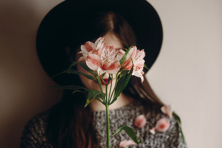stylish hipster girl in hat holding pink flowers and petals on sweater growing. boho woman with beautiful alstroemeria in hands. focus on flower. eco concept. save and protect Stock Photo