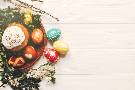 stylish easter eggs and easter bread cake and flowers on wooden background flat lay. modern eggs natural dyed. space for text. happy easter greeting Stock Photo