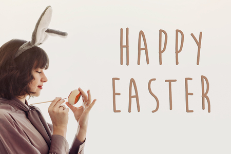 happy easter text, greeting card with beautiful woman in bunny ears painting easter egg in light, isolated with space for text. young girl witt rabbit ears holding colored egg. easter hunt
