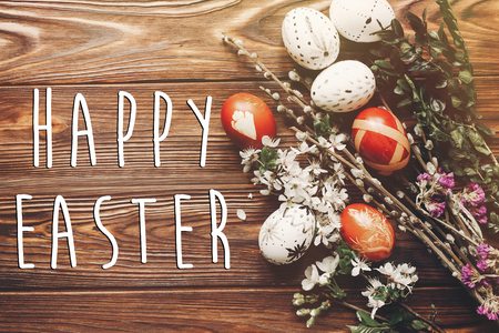 happy easter text on stylish easter eggs with white flowers and buds on wooden background flat lay. modern eggs and natural dyed with herbs