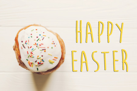 happy easter text on delicious easter bread cake with colorful icing top view on wooden background. homemade bread for traditional easter feast. flat lay. minimalism