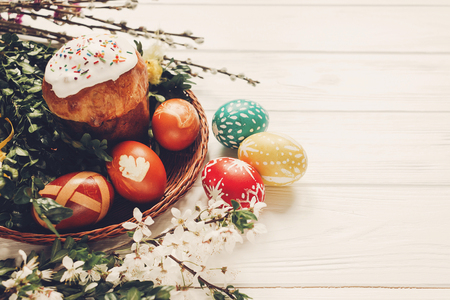 stylish easter eggs and easter bread cake and flowers on wooden background. modern eggs natural dyed. willow buds and wicker basket. space for text. happy easter greeting