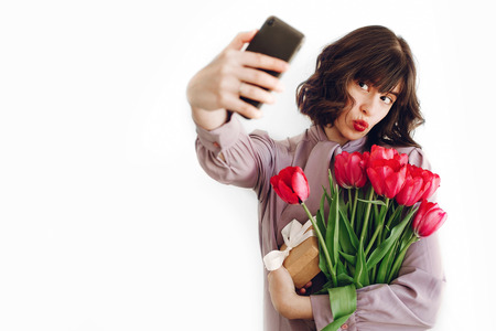 happy stylish girl making selfie with pink tulips and gift box with ribbon on white background.