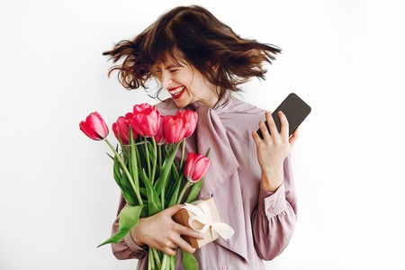happy stylish girl smiling and dancing with phone and holding pink tulips and gift box on white background. happy mothers or womens day concept. emotional moment of happiness Standard-Bild