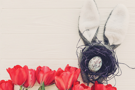 bunny ears and stylish egg in nest and tulips on white wooden background flat lay. space for text. creative spring easter image. seasons greeting card mock-up. happy easter concept