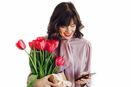 happy mothers or womens day concept. happy stylish girl with pink tulips and gift box with ribbon looking at phone and smiling on white background. young hipster woman with flowers