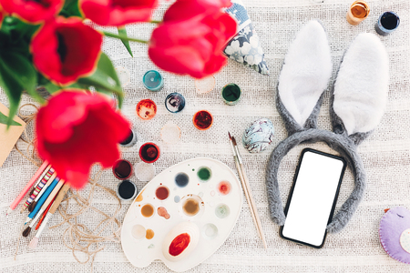 happy easter concept. bunny ears and phone with empty screen and easter egg on rustic background flat lay with space for text. creative easter image. seasons greeting card mock-up