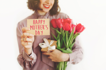happy mothers day text on greeting card. happy woman holding  card and pink tulips and gift box, smiling on white background. happy mothers day concept. young mom with flowers. Standard-Bild