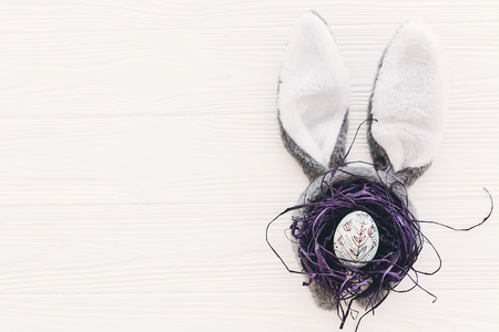 happy easter concept. bunny ears and stylish egg in nest on white wooden background flat lay with space for text. creative easter image. seasons greeting card mock-up