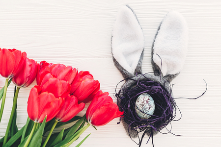 happy easter concept. bunny ears and stylish egg in nest  and tulips on white wooden background flat lay with space for text. creative easter image. spring seasons greeting card mock-up