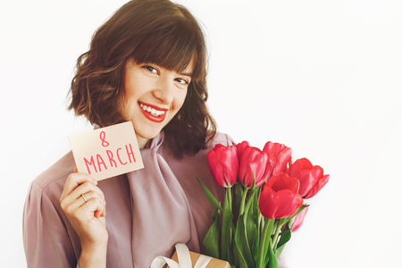 happy womens day text on greeting card. 8 march. happy stylish girl holding card and pink tulips and gift,  smiling on white background. happy womens day concept. woman with flowers. Standard-Bild