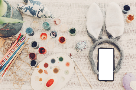 happy easter concept. bunny ears and phone with empty screen and easter egg paint on rustic background flat lay with space for text. creative easter image. greeting card mock-up
