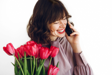 happy mothers or womens day concept. happy stylish girl talking on phone and holding pink tulips and gift box with ribbon, and smiling on white background. young hipster woman