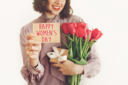 happy womens day text on greeting card. happy stylish girl holding card and pink tulips and gift, smiling on white background. happy womens day concept. young woman with flowers.