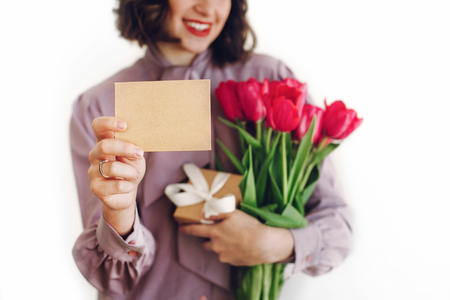 happy stylish girl holding greeting card with space for text and pink tulips and gift box with ribbon and smiling on white background. happy mothers or womens day concept. young woman with flowers.