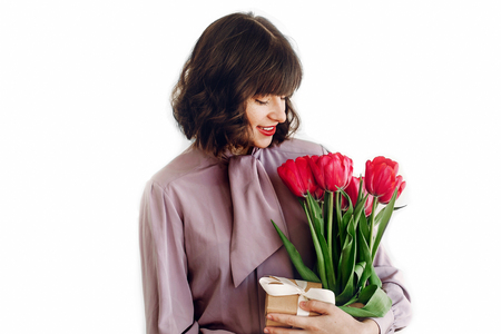 happy stylish girl holding pink tulips and craft gift box with ribbon and smiling on white background. happy mothers or womens day concept. young woman with flowers. space for text Standard-Bild
