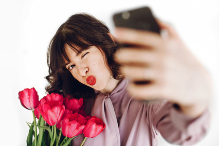 happy stylish girl taking selfie on phone and holding pink tulips and gift box on white background. happy mothers or womens day concept. young hipster woman smiling with flowers