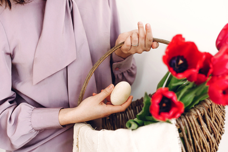 easter hunt concept. beautiful stylish girl holding basket with pink tulips and natural easter eggs on white background isolated. happy child looking for egg. space for text