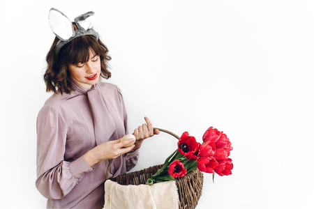 easter hunt concept. beautiful stylish girl in bunny ears holding basket with pink tulips and natural easter eggs on white background isolated. happy woman looking for egg. space for text
