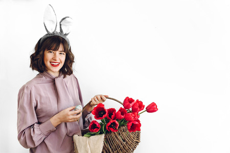 easter hunt concept. beautiful stylish girl in bunny ears holding basket with pink tulips and easter eggs on white background isolated.happy woman holding painted egg.  space for text Standard-Bild