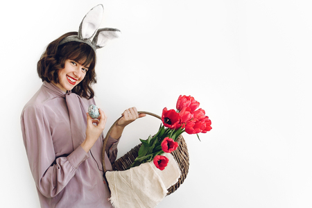 beautiful stylish girl in bunny ears holding basket with pink tulips and easter eggs on white background isolated. easter hunt concept. happy woman holding painted egg.  space for text