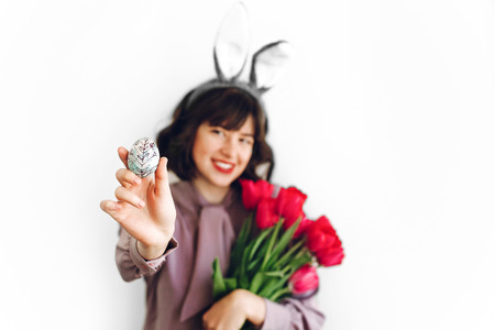 happy Easter. beautiful stylish girl in bunny ears and pink tulips holding easter egg on white background isolated. easter hunt concept. happy woman holding painted egg. seasons greetings