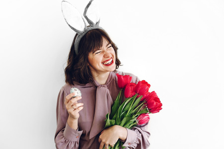 beautiful stylish girl smiling with bunny ears and pink tulips holding easter egg on white background isolated. easter hunt concept. happy woman holding painted egg. seasons greetings